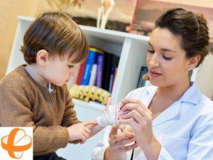 Cirujana plástica atendiendo en consulta médica la mano de un niño. Atención Pediátrica